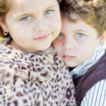 Sierra (6) and her brother Joe (4) look darling together wearing a leopard print Chabré jacket and a white long-sleeved, brown pin-striped shirt and brown knit vest. Outfits provided by The Ragamuffin Shop.