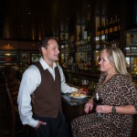 Play-by-play sports broadcaster Darren Goldwater wears Polo Ralph Lauren menswear while enjoying a bar appetizer of focaccia croutons and the house pimento salad with his wife, Ryan Nelson, at Burtons. Ryan wears a knee length leopard print dress by Michael Kors. Clothing provided by Belk in Mount Pleasant Towne Centre.