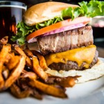 The popular Wilbur burger at Triangle Char & Bar featuring grass fed beef, pork belly and cheddar cheese served with a locally crafted beer.