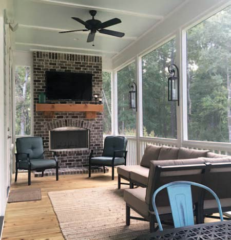 The Caldwell family's screened-in porch functions as an outdoor living room, complete with a television and wood-burning fireplace.