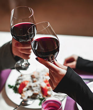 Charleston Wine Pairings - two glasses of wine raised during a date