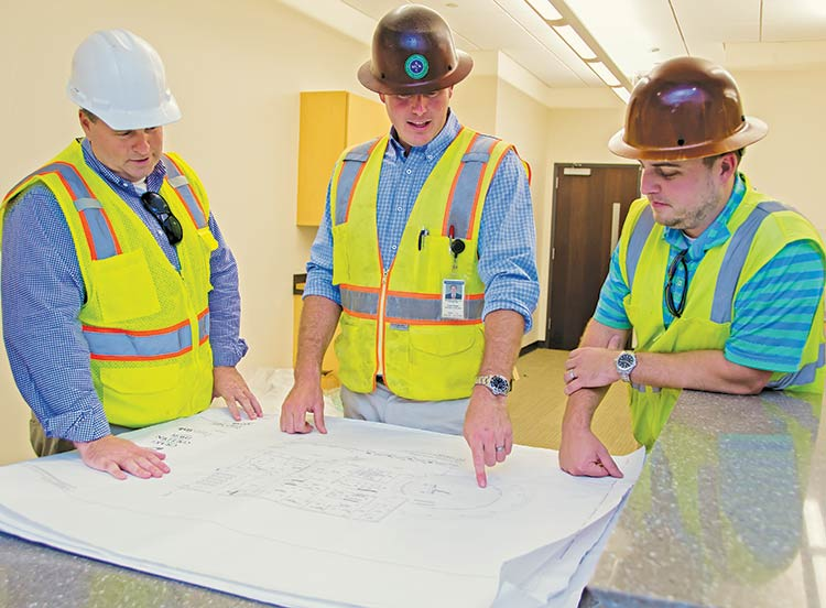Matt Farrell, Brooks Blumenthal and Bryce Howeie review floor plan for the new Town Hall
