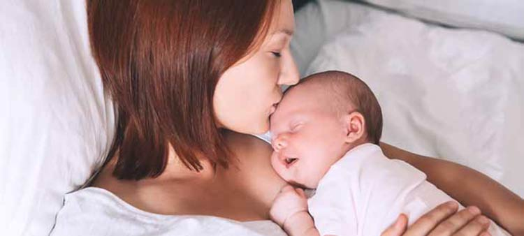 A mother with her infant. Postpartum care article.