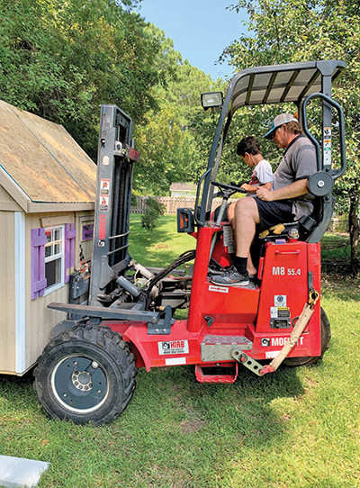 Cayden helps move the clubhouse into his backyard.