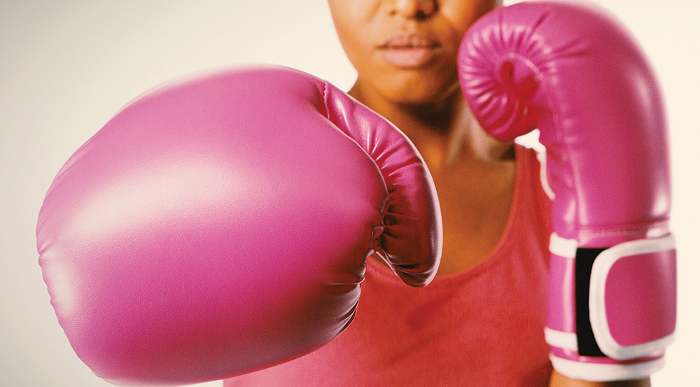 Fighting cancer - Boxer with pink gloves photo
