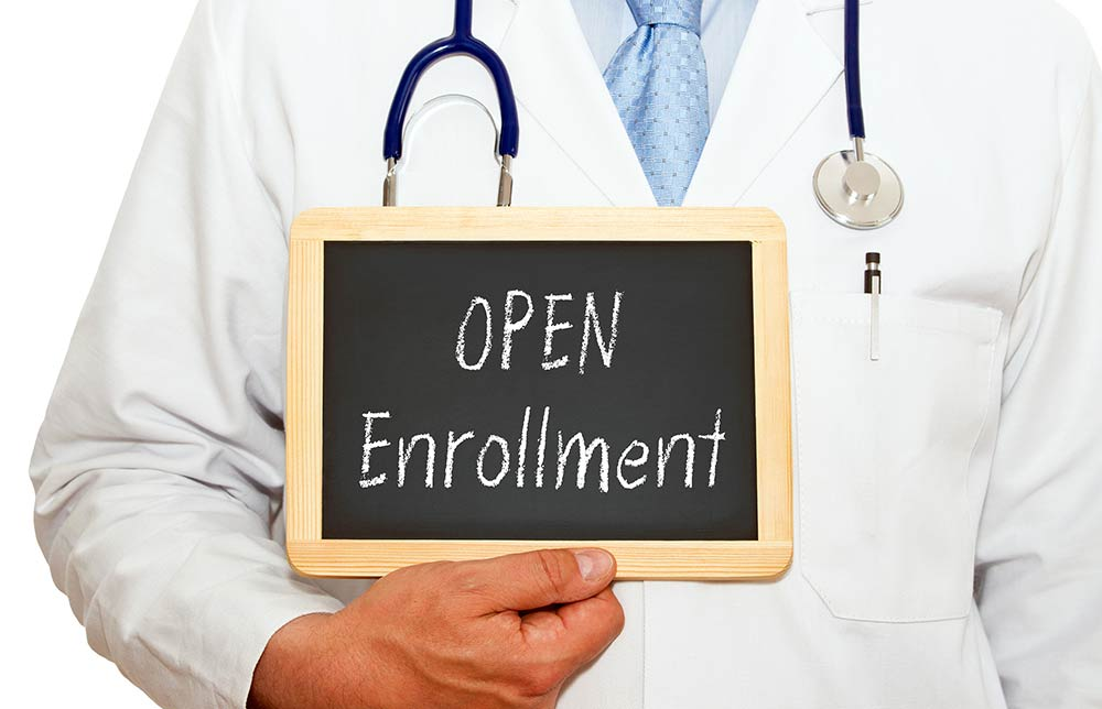 A man holding an 'open enrollment' sign