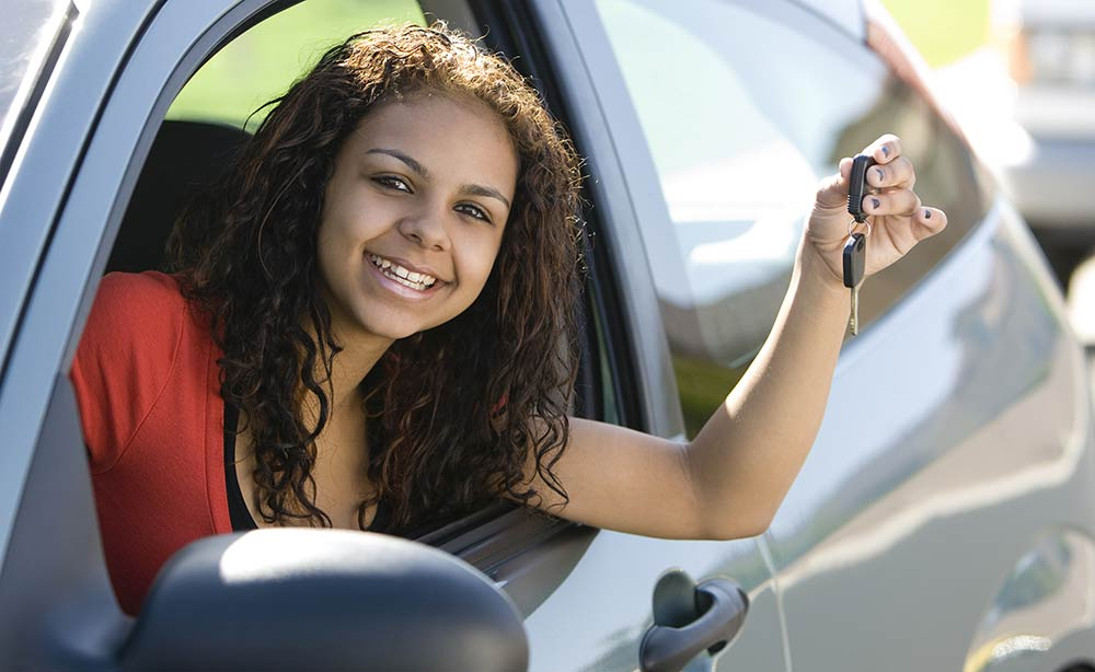 A teen smiles with car keys in her hand