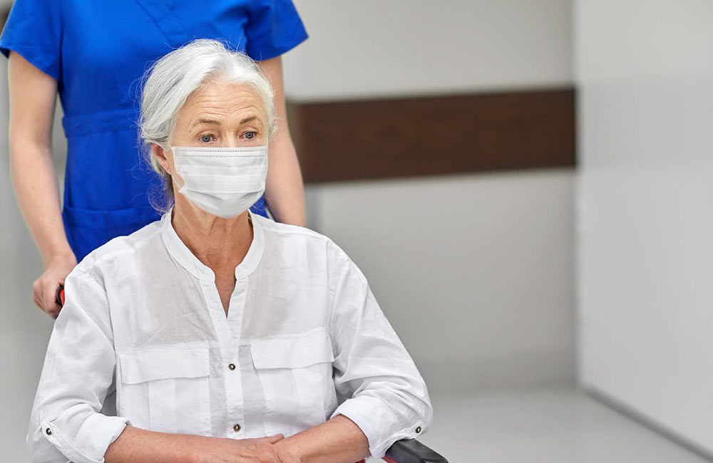 Photo of a woman at the hospital in a wheelchair wearing a mask for the Locals Overcome the COVID-19 Virus article