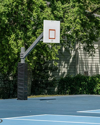 Backboard with no hoop on a basketball court closed during the COVID-19 Pandemic