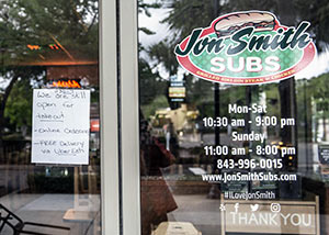Jon Smith Subs. A hand-written sign reads.., 1130-7. We are still open for takeout -online ordering - FREE Delivery via Uber Eats