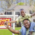 A son and his father smile in celebration after their house has been sold.