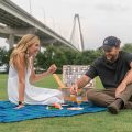 A couple enjoys a picninc with the Arthur Ravenel Bridge as a backdrop