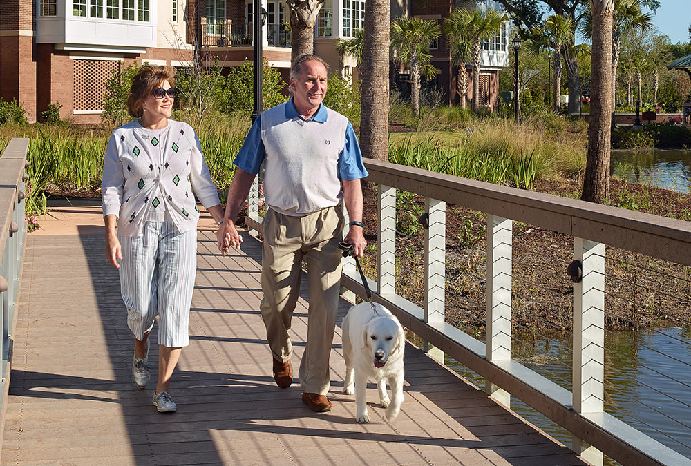 A couple walking a dog at Bishop Gadsden in James Island, SC.