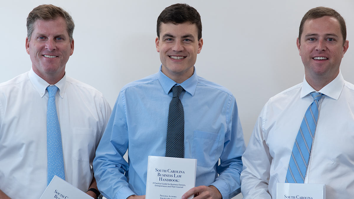 Jim Buxton, Nate Johnson and Brian Collie of Buxton & Collie Attorney at Law holding their South Carolina Bar publication,South Carolina Business Law Handbook: A Practical Guide for Business Owners, Entrepreneurs, and Their Counsel.