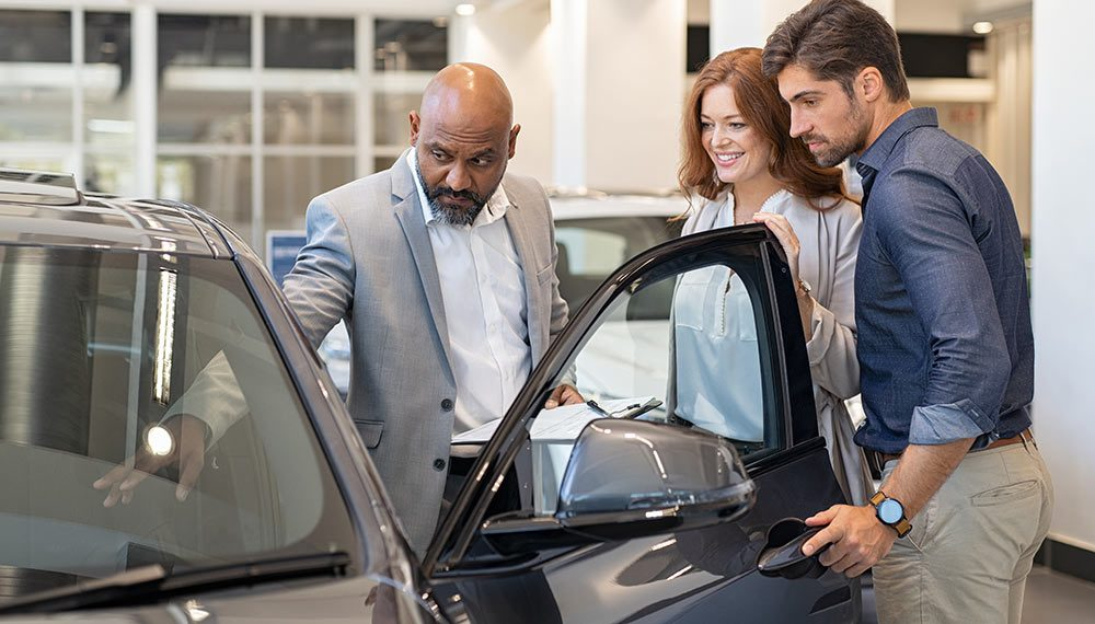 An auto sales manager showing a vehicle to a couple.