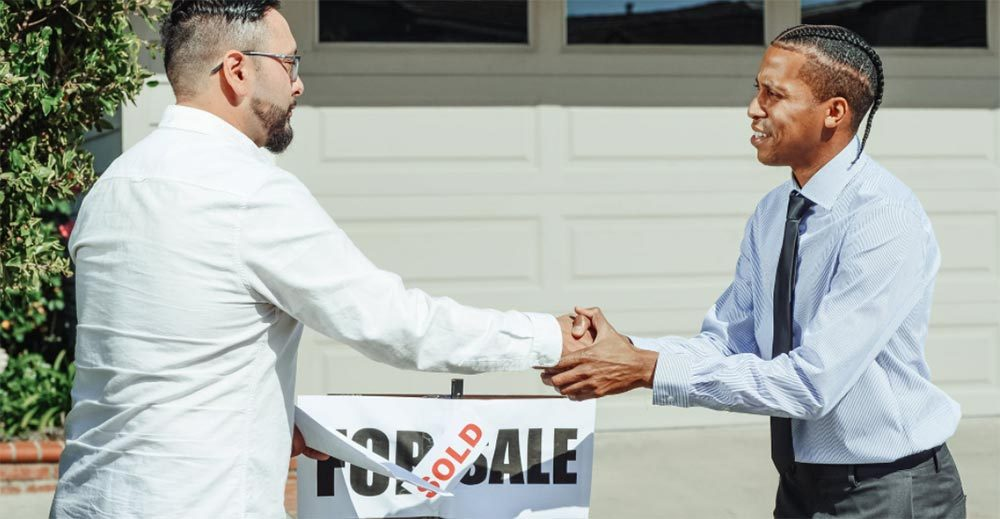 A realtor and home buyer sake hands after the sale of a home. Photo credit Kindel Media on Pexels.
